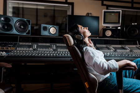 Foto de pretty sound producer listening music in headphones while sitting in office chair in recording studio - Imagen libre de derechos