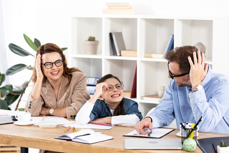Photo pour cheerful kid in glasses sitting with happy parents in office - image libre de droit