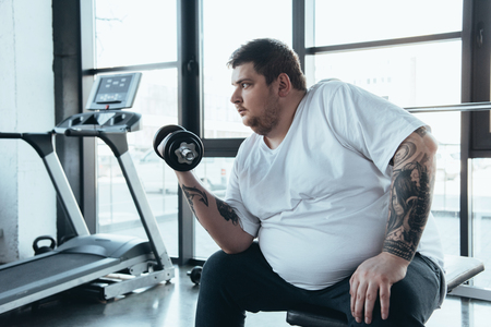 Foto de Overweight tattooed man exercising with dumbbell at sports center - Imagen libre de derechos