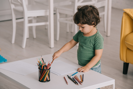Photo pour Kid in green t-shirt with color pencils and papers in living room - image libre de droit