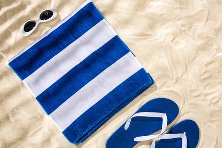 Photo pour Top view of white blue striped folded towel, retro sunglasses and flip flops on sand - image libre de droit