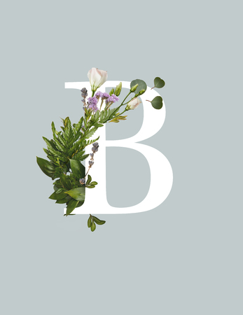 White letter B with eustoma flowers and green fern leaves isolated on grey background