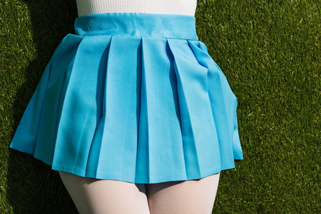 Photo for Cropped view of girl in blue skirt lying on grass - Royalty Free Image