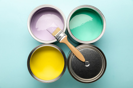 Photo pour Top view of tins of paints and brush on blue surface - image libre de droit