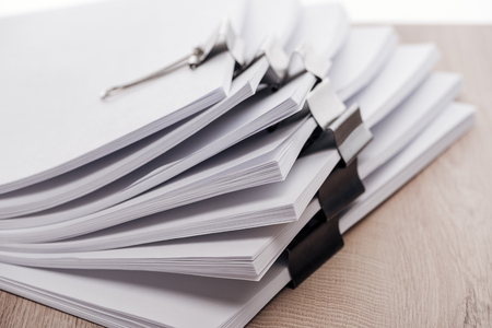 Photo pour Close up view of stacks of blank paper with metal binder clips - image libre de droit