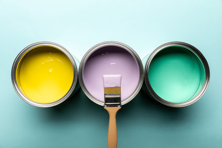 Photo pour Top view of three tins with paints and brush on blue surface - image libre de droit