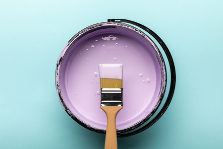 Photo for Top view of bucket with purple paint and brush on blue background - Royalty Free Image