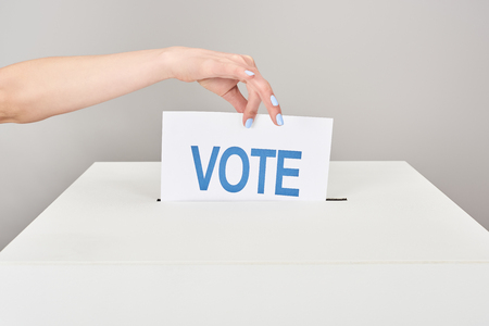 Photo pour Partial view of woman putting card with vote in box isolated on grey background - image libre de droit