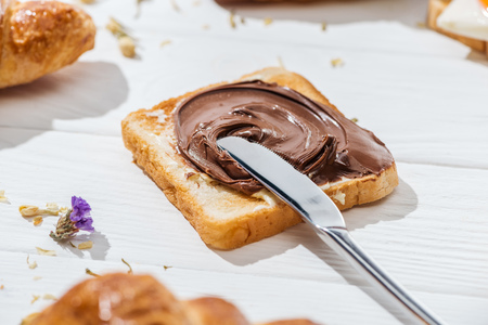 Photo pour Selective focus of toast with chocolate cream and knife on white background - image libre de droit