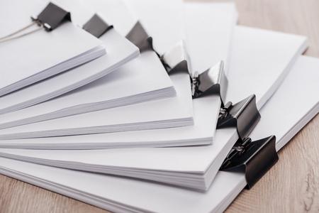Photo pour Arranged stacks of blank paper with metal binder clips on wooden desk - image libre de droit