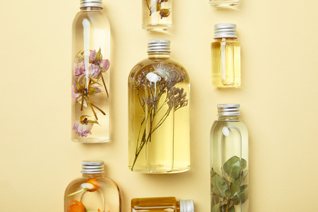 Foto de Top view of transparent bottles with natural beauty products and dried wildflowers on yellow background - Imagen libre de derechos