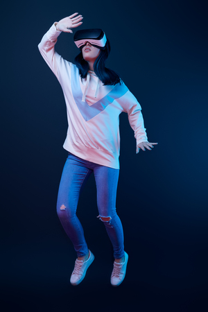 Photo for Young woman gesturing while using virtual reality headset and jumping on blue background - Royalty Free Image