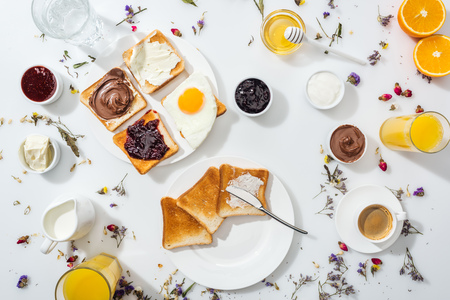 Foto de Top view of plates with tasty toasts near drinks and oranges on white background - Imagen libre de derechos