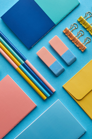 Photo pour Top view of notebooks and colorful stationery isolated on blue background - image libre de droit