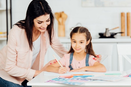 Photo pour happy mother standing near paper near happy daughter looking at camera - image libre de droit