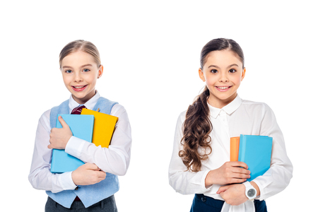 Photo pour happy schoolgirls in formal wear with books looking at camera Isolated On White - image libre de droit