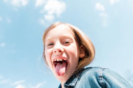 Photo pour Low angle view of happy kid showing tongue under sky background - image libre de droit