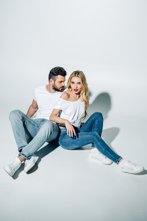 Photo for Handsome man sitting and looking at attractive blonde girl on white background - Royalty Free Image