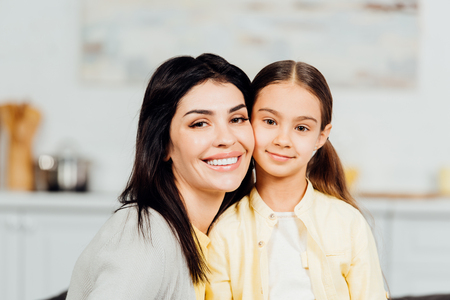 Photo pour Happy child looking at camera with cheerful mother at home - image libre de droit