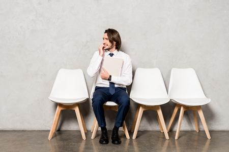 Photo pour worried man in formal wear holding folder while waiting job interview - image libre de droit