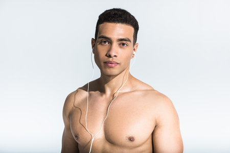 Photo pour handsome athletic man with muscular torso listening music in earphones on white - image libre de droit