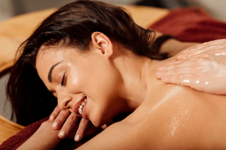 Photo pour smiling young woman lying with closed eyes during ayurvedic massage - image libre de droit