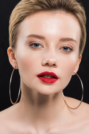 Photo for pretty naked young woman in earrings looking at camera isolated on black - Royalty Free Image