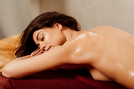 Photo pour relaxed young woman lying with closed eyes on massage table - image libre de droit
