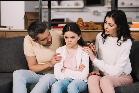 Photo pour worried parents touching offended daughter sitting on sofa with crossed arms - image libre de droit