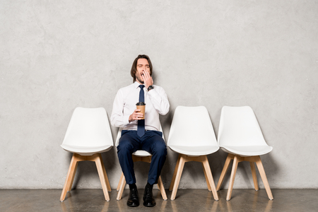 Photo for tired handsome man yawning while holding paper cup and sitting on chair - Royalty Free Image