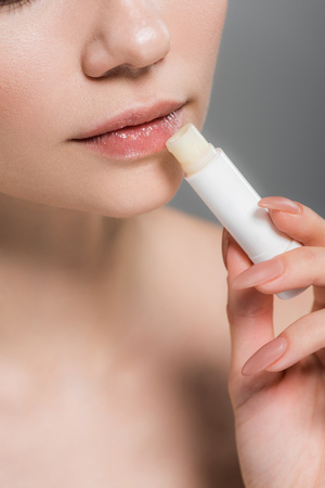 Photo pour cropped view of girl holding lip balm near lips isolated on grey - image libre de droit