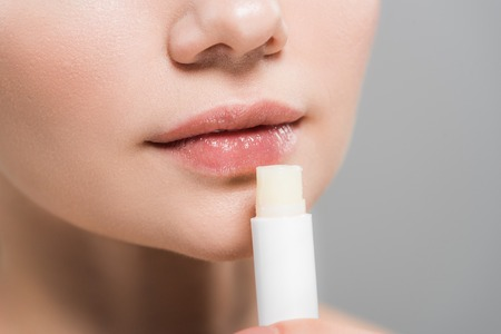 Foto de cropped view of young woman holding lip balm isolated on grey - Imagen libre de derechos