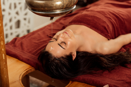 Photo pour relaxed young woman lying under shirodhara vessel during ayurvedic procedure - image libre de droit