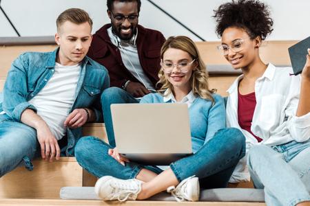 Photo pour smiling multicultural students using laptop in lecture hall - image libre de droit