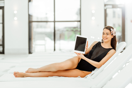 Photo pour smiling barefoot woman lying on sunbed and showing digital tablet with blank screen - image libre de droit