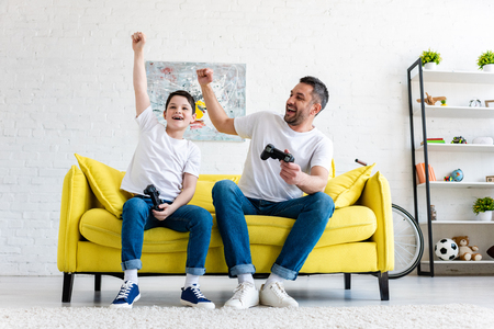 Father and son cheering while playing Video Game on couch at home