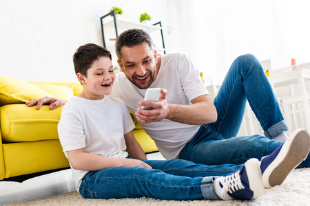 Photo pour Happy father and son using smartphone in living room - image libre de droit
