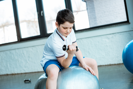 Photo pour Cute boy sitting on fitness ball and working out with dumbbell at gym - image libre de droit
