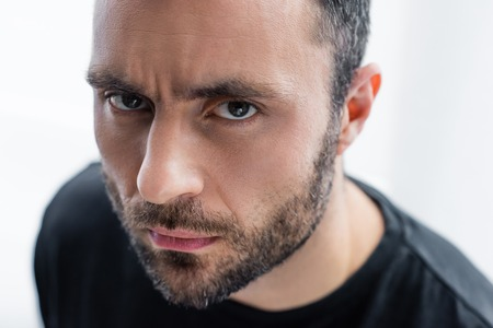 Photo pour Portrait of serious, handsome bearded man looking at camera - image libre de droit