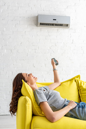 Photo for Pretty young woman lying on yellow sofa under air conditioner and holding remote control - Royalty Free Image