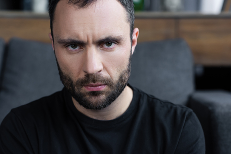 Photo for Serious handsome bearded man in black t-shirt looking at camera - Royalty Free Image