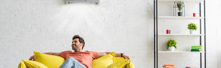 Photo for Panoramic shot of handsome man sitting on yellow sofa under air conditioner at home - Royalty Free Image