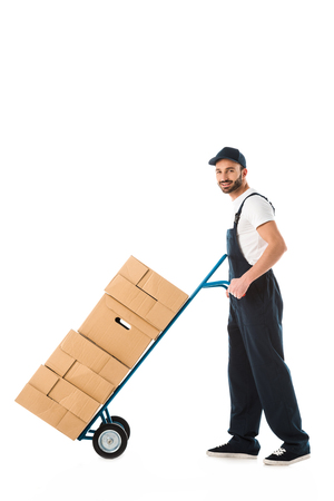 Photo for Smiling delivery man transporting hand truck loaded with carton boxes isolated on white background - Royalty Free Image