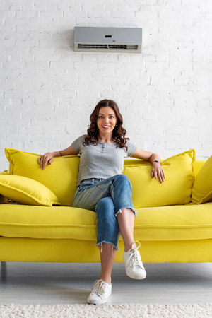 Photo for Beautiful smiling woman sitting on yellow sofa under air conditioner at home - Royalty Free Image