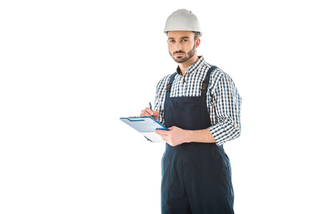 Photo pour Serious bearded construction worker writing on clipboard and looking at camera isolated on white background - image libre de droit