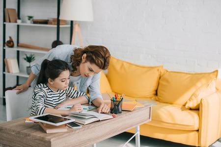 Foto de beautiful woman helping adorable daughter doing schoolwork at home - Imagen libre de derechos