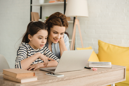 Photo for surprised mother and daughter using laptop while doing homework together - Royalty Free Image