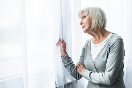sad senior woman with grey hair looking at window