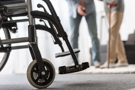 Foto de selective focus of adult son and senior mother with wheelchair on foreground - Imagen libre de derechos