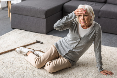 Foto de senior woman with migraine sitting on carpet and touching forehead with hand - Imagen libre de derechos